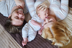 Mom and dad playing with his baby son on the bed. Happy family concept.  Stock Photography