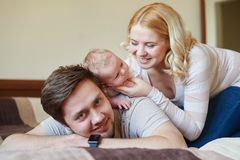 Mom and dad playing with his baby son on the bed. Happy family concept.  Stock Photos