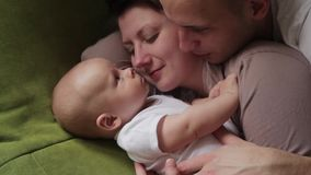 Mom and dad playing with his baby son on the bed. Happy family concept stock footage