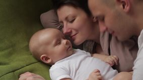 Mom and dad playing with his baby son on the bed. Happy family concept stock video