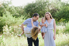 Mom and dad playing on the nature and hugging two daughters. Family, childhood, family values, life style Stock Image