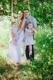 Mom and dad playing on the nature and hugging two daughters Royalty Free Stock Photo