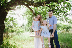 Mom and dad playing on the nature and hugging two daughters Royalty Free Stock Image