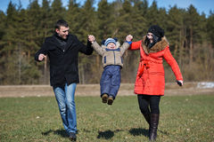 Mom and dad raise child up Stock Image