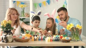 Mom, dad, son and daughter sitting and drawing on Easter eggs together stock video footage