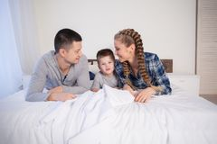 Mom dad and son lie on the bed at home dream. Mom dad and son lie on the bed at home woke up Royalty Free Stock Photo
