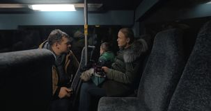 Mom, dad and son traveling bus in the evening and using cellphones stock footage