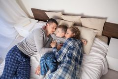 Mom and dad and little boy in the bedroom. Mom dad and son woke up in the morning Royalty Free Stock Images