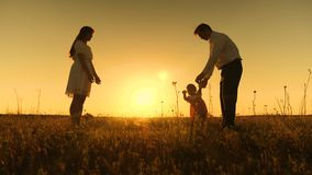 Mom and dad are taught to go to small daughter, young beautiful family in park with a child at sunset royalty free stock images
