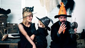 Mom, dad and their son are celebrating Halloween holiday. Family in costumes have fun on halloween. Halloween party and. Celebration concept stock video footage