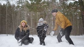 Mom and dad are throwing a snow making a snowfall for their son in slow motion. stock footage