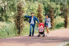Mom and dad are walking in the park with their daughter in a stroller, a beautiful sunny day, a beautiful family stock photo