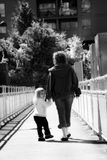 Mom and Daughter. Walking away from camera little girl looking back Royalty Free Stock Photo