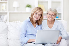 Mom and daughter. Families with a laptop on the couch Stock Photo