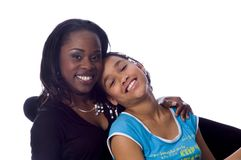 Mom & daughter. African American Mother and daughter sitting in a cosy chair smiling on a white background Stock Photo