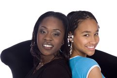 Mom & daughter. African American Mother and daughter sitting in a cosy chair smiling on a white background Royalty Free Stock Photo