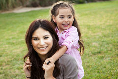 Mom and daughter. Diverse mom and daughter sitting in the grass royalty free stock images