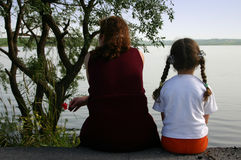 Mom & Daughter. Watching lake. Mother and girl stock photography