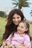 Mom and daughter. Loving mom and daughter sitting in the grass royalty free stock image
