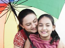 Mom and daughter. Mother and daughter with a rainbow umbrella stock photo