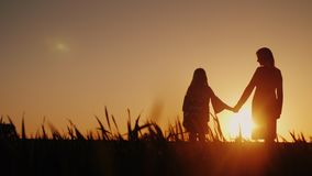 Mom and daughter are admiring the sunset, holding hands. Happy childhood concept stock image