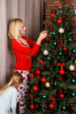 Mom with daughter adorns tree Royalty Free Stock Photos