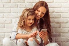 Mom, Daughter And Gadget Stock Photos