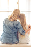 Mom and daughter. Back view of beautiful blonde women and her teenage daughter hugging and looking through the window, sitting at home Stock Image