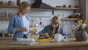 Mom and daughter bake muffins in the kitchen together. A woman puts the dough in a selikon baking dish with a wooden. Spoon. Girl helps her mom stock video