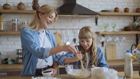 Mom and daughter bake pancakes in the kitchen together. Girl helps her mom get dough. 4K. Mom and daughter bake pancakes in the kitchen together. Girl helps her stock footage