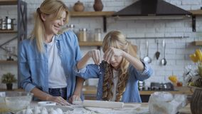 Mom and daughter bake pizza in the kitchen together. Girl helps her mom to roll out the dough with a rolling pin. 4 k. Mom and daughter bake pizza in the kitchen stock video footage