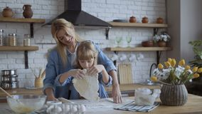 Mom and daughter bake pizza in the kitchen together. girl helps her mom to roll out the dough with a rolling pin. 4K. Mom and daughter bake pizza in the kitchen stock video footage
