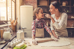 Mom and daughter baking. Beautiful young mom and her cute little daughter are playing and smiling while baking in kitchen at home Stock Photos