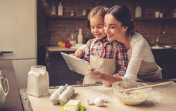 Mom and daughter baking. Beautiful young mom and her cute little daughter are using a digital tablet and smiling while baking in kitchen at home Stock Photos
