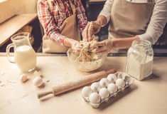 Mom and daughter baking. Cropped image of cute little girl and her beautiful mother kneading dough while preparing it for baking Royalty Free Stock Photography