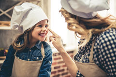 Mom and daughter baking. Cute little girl and her beautiful mom in aprons and chef hats are touching noses and smiling while kneading the dough in the kitchen Royalty Free Stock Photo