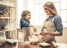 Mom and daughter baking. Cute little girl and her beautiful mom in aprons are smiling while preparing dough for baking in the kitchen Stock Photo