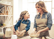 Mom and daughter baking. Cute little girl and her beautiful mom in aprons are talking and smiling while kneading the dough in the kitchen Royalty Free Stock Photo