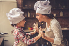 Mom and daughter baking. Cute little girl and her beautiful mother in chef hats are playing and smiling while baking in kitchen at home Stock Photography