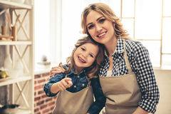 Mom and daughter baking. Cute little girl and her beautiful young mom are hugging, looking at camera and smiling while baking in kitchen Royalty Free Stock Images