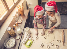 Mom and daughter baking. High angle view of beautiful young mom and her cute little daughter in Santa hats using cookie cutters while baking in kitchen at home Royalty Free Stock Photos