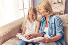 Mom and daughter. Beautiful blonde women in jeans shirt and her teenage daughter are looking through photos and smiling while sitting on couch at home Royalty Free Stock Image