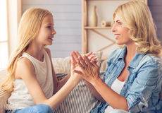Mom and daughter. Beautiful blonde women in jeans shirt and her teenage daughter are playing with hands, looking at each other and smiling while sitting on couch Stock Image