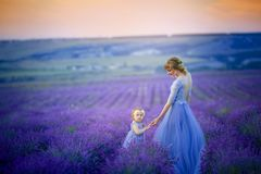 Mom and daughter in beautiful dresses in lavender field.  royalty free stock photo