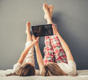 Mom and daughter. Beautiful women and her cute little daughter are using a digital tablet while lying on bed with their legs raised Stock Photos