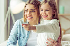 Mom and daughter. Beautiful young mom and her little daughter are cuddling, smiling, looking and pointing away while sitting on sofa at home Stock Photo