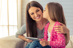 Mom and daughter. Beautiful young mother and her cute little daughter are using a tablet and smiling, sitting on sofa at home. Girl is kissing her mom on cheek Stock Photos
