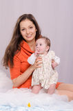 Mom and daughter on the bed six-month. Mom and daughter on the couch six-month stock photo