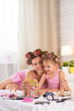 Mom and daughter in the bedroom on the bed in the curlers make u Royalty Free Stock Photo