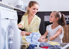 Mom and daughter with bin near washing machine Royalty Free Stock Photo
